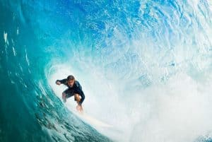 """Photo of a surfer to illustrate, """"riding the waves of change"""" that come with life storms and how to survive the storms of life."""