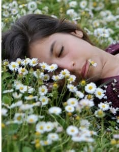 photo of a woman in a field of daises. It represents getting out in nature.