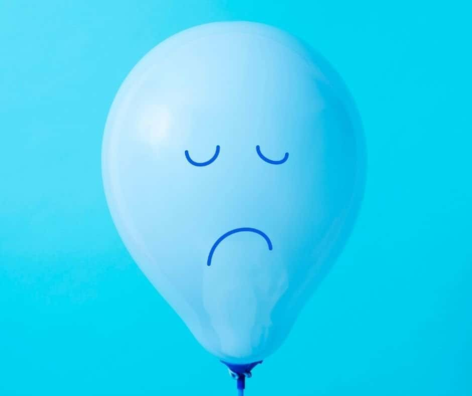"""photo of a balloon with a sad face on a blue background- to represent """"why should I smile when it hurts inside""""."""