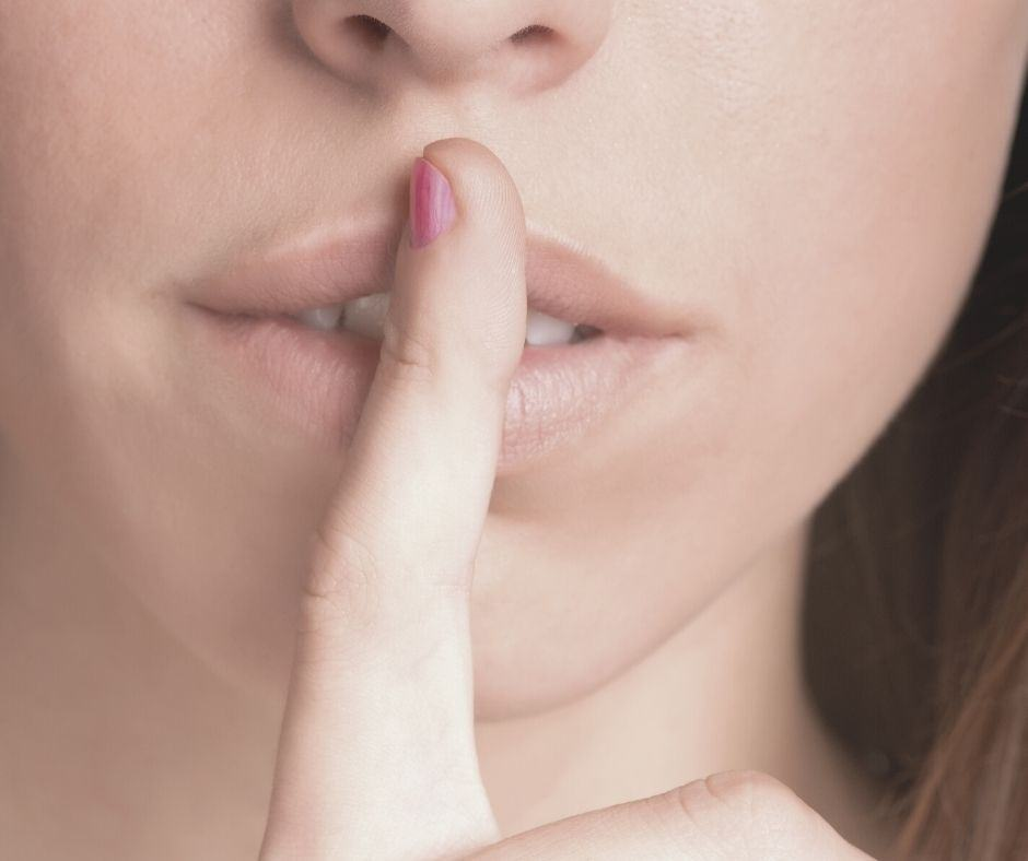 """Photo of a woman with her finger to her lips as if to say, """"shhhh, it is a secret."""""""